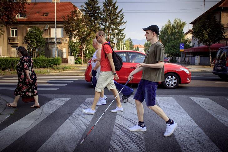 Slijepi korisnik prelazi cestu pomoću bijelog štapa