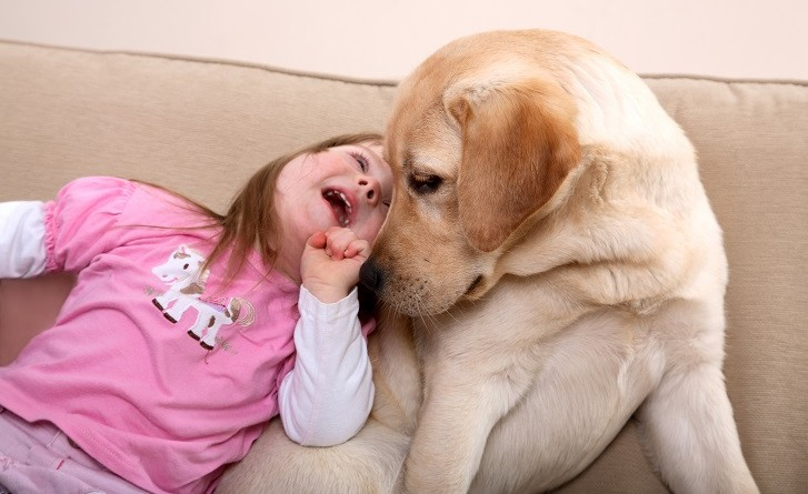 A young girl with Down Syndrome sitting on a couch with a puppy.