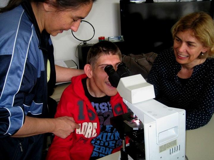 korisnik uči gledati na mikroskop za vrijeme posjete strucnjaka